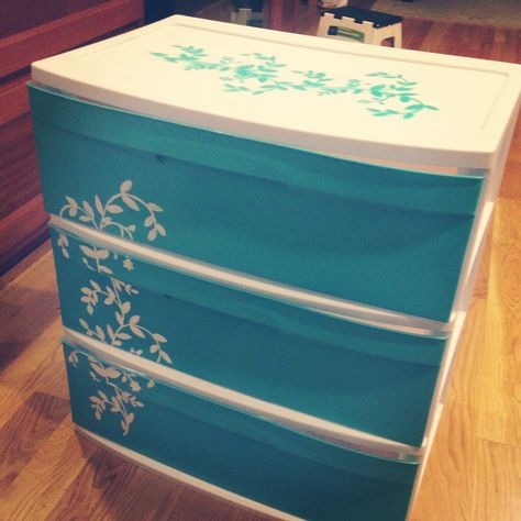 SO EASY. I decorated a 3-drawer cheap plastic storage container from Walmart. Just take the 3 drawers outside, put them on newspaper and use your favorite colored spray paint (can even color coordinate with bedspread!) and use a stencil for a more professional-looking design.