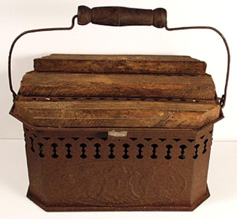 "Buggy Foot Warmer $160.00 Sheet metal, pierced on sides, lid to let heat through. 2 embossed lions & ""1"" on front, back. Orig. wood strips on top to rest feet. Lid opens to reveal a bail handled bucket which holds coals. Outer bail handle, too. No rust-through metal. 9"" L x 5 1/2"" W x 4 3/4"" H."