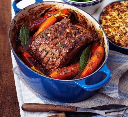 Sunday roast dinner. Pot-roast beef with onion gravy served with roast potatoes and vegetables  - BBC Good Food