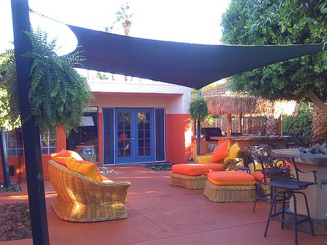Shade Sails, cobalt accents and orange cushions make for a fun patio.  Palapa covered bar and BBQ area