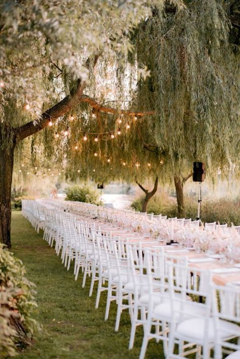 Under the willowing branches of the weeping willows along the riverside in Italy, Nicole and Jordon tied the knot at a romantic outdoor wedding. Valeria Ferrari planned a pretty in pink wedding affair bursting with garden roses and hydrangeas that immediately had us falling in love with every delicate detail. The dreamy reception under twinkling lights with a lush floral runner in shades of pink is simply majestic and each photo from Halo Wedding has us swooning. View full post