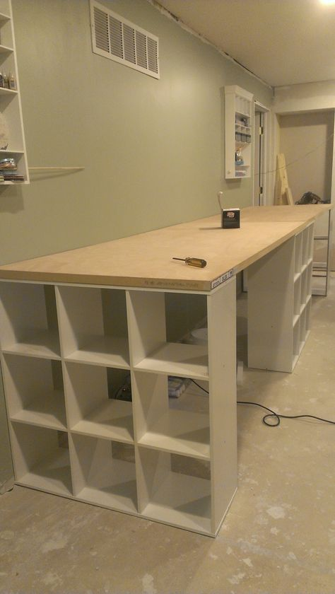 Craft room progression...... DIY work table... Three 9 cube shelves from lowes Two hollow doors from lowes. This work table is 13 feet long. (***Cannot find the original source for this image anywhere on the web!***)