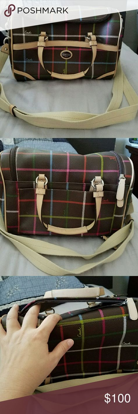 Coach Travel Bag Coach Travel Bag in the brown plaid material. Used only a handful of times, but not for travel.   3rd picture shows a zipper opening on the back side of the purse. Close the zipper and you have an extra exterior pocket. Open the zipper and you can slip the bag over the pull handle of your suitcase.  1 magnetic pocket in front. Interior has 2 elastic side pockets and 1 zippered pocket.   Clean inside and out. Removeable strap for crossbody wear. Coach Bags Travel Bags