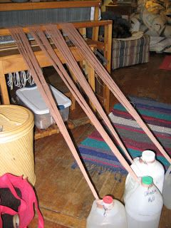 Water-filled jugs provide resistance when winding the warp onto back beam. Great idea for me because I have to do everything all by my lonesome.