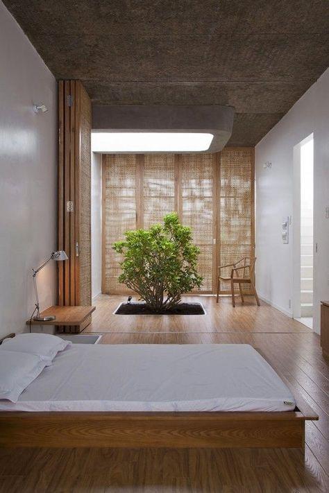 Une chambre à  coucher avec un lit japonais et un bonsai