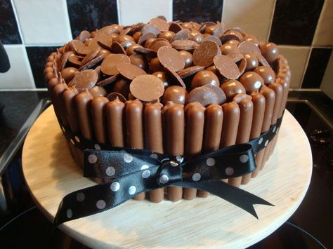 Chocolate cake, with chocolate buttercream, chocolate fingers around the outside and maltesers and chocolate buttons on the top.