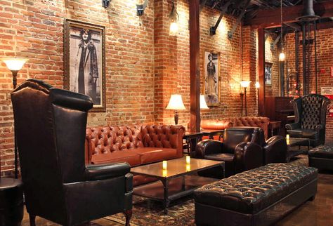 Brick effect wallpaper, black and white pictures on the wall, chesterfield chairs.  10 Best Speakeasy Bars in America | Architectural Digest