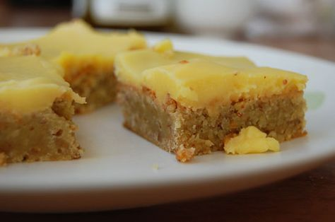 Lemon Curd Bars - a cross between a power bar -- because the base is high in protein as it's made from nuts and eggs -- and a lemon bar, because it has a delectable lemony topping. Dairy and gluten free, it's also grain free! High in nutrients and flavor, low in allergens.  Lightly sweetened with honey, I can easily imagine it acting as a power bar after a workout, but we eat it as dessert around here.