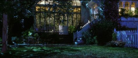 Nighttime exterior view of the conservatory and kitchen door of the house in the movie Practical Magic.