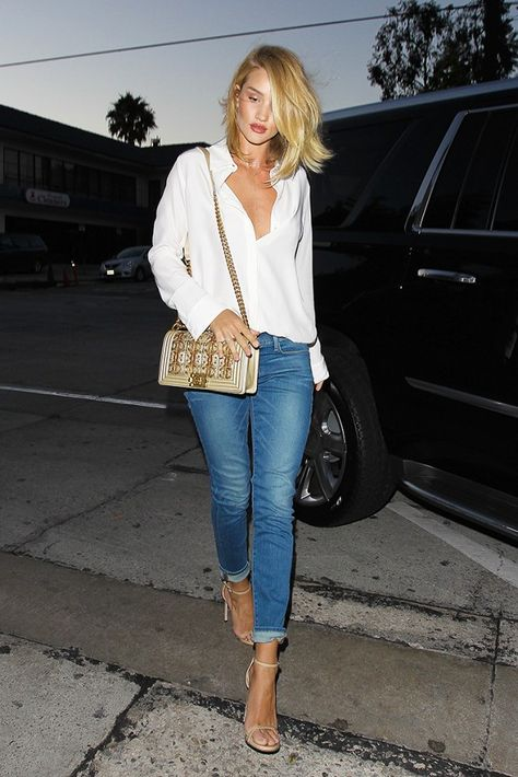 Rosie Huntington-Whiteley wears a silk button-down blouse, cuffed jeans, nude ankle-strap heels, and a Chanel Boy bag