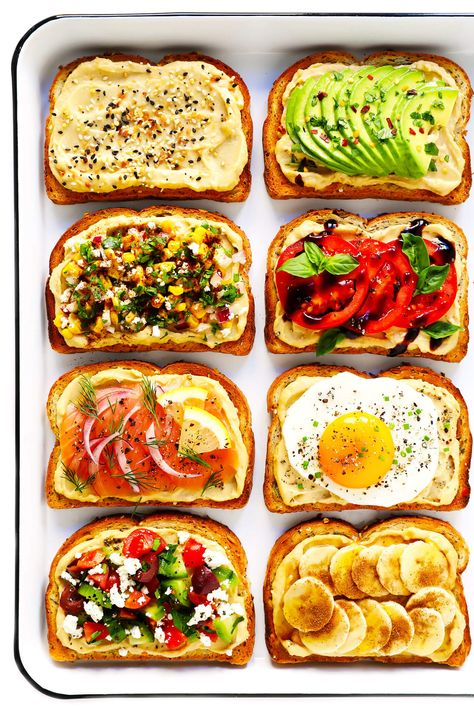 """Hummus Toast is fun to customize with your favorite toppings, and makes for a delicious easy breakfast, lunch, dinner or healthy snack! Read more for details on 8 of our favorite toppings -- """"everything"""", avocado, elote, tomato basil, lox, fried egg, mediterranean or honey banana. 