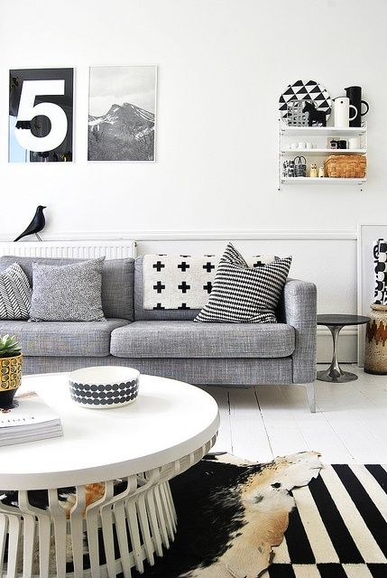 Black and white living room with Ikea sofa and warming grey, tan accents.  Love the stripe rug, bold patterns throughout. (photo by deborah moir for amm)