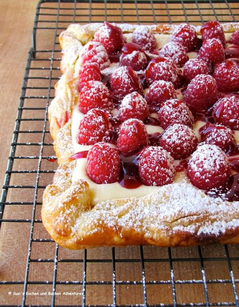 1 sheet puff pastry, thawed but still cold 4 oz. cream cheese, softened 1/3 cup sugar, plus more for sprinkling 2 Tbsp. heavy cream 1/3 cup lemon curd  1 pint raspberries  1/4 cup seedless raspberry jam warmed powdered sugar