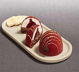 Dôme doré chocolat et cœur banane, Brake, déc15 cœur mousse de banane et uruits rouges, mousse au chocolat blanc. Décor velours rouge et stries dorées.