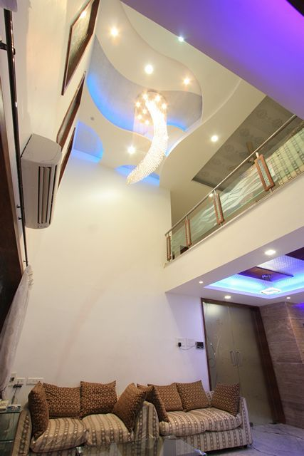 Perfect Double Height Ceiling In The Living Area Has An Exclusive Chandelier Hung  On Curve Design False Ceiling With Coloured Conceal Lights. Part 30