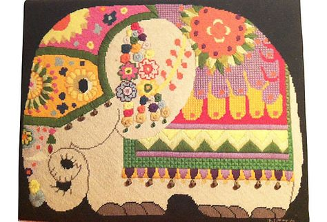 A handmade needlepoint elephant, embellished with beads and bells.