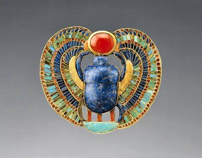 A scarab of lapis lazuli with falcon wings, supporting a red disk of the new-born sun