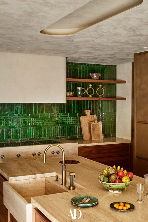 When they were ready to downsize from their nearby villa, a couple turned to their architect son to combine three stellar apartments into their dream home. The kitchen built-in storage was made out of travertine, oak wood, and walnut. The credenza is adorned with green Moroccan zellige handmade enamel tiles. #kitchens #kitchenideas #kitcheninspo #design #Minimalist #green #backsplash #tile #wood #sink #storage #cuttingboards #decor #walnut #oak #travertine #credenza #storage