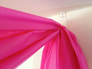 Tip Use small Command hooks at corners. Gather plastic tablecloth and wrap with twist tie. Hook twist tie loop onto Command hook. Add tulle to completely cover the Command hook