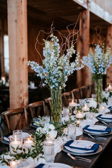 Simple reception centerpieces with a big impact. Tall blue delphinium arrangements with curly willow branches, greenery runner, candles and small accent designs. Floral: Wildflowers LLC Photo: Eden Ingle Photography Source by Blue Wedding Decorations, Wedding Reception Centerpieces, Wedding Reception Flowers, Branch Centerpiece Wedding, Wedding Ideas Blue, Colorful Wedding Centerpieces, Pastel Blue Wedding, Wedding Ceremony, Wedding Table Flowers