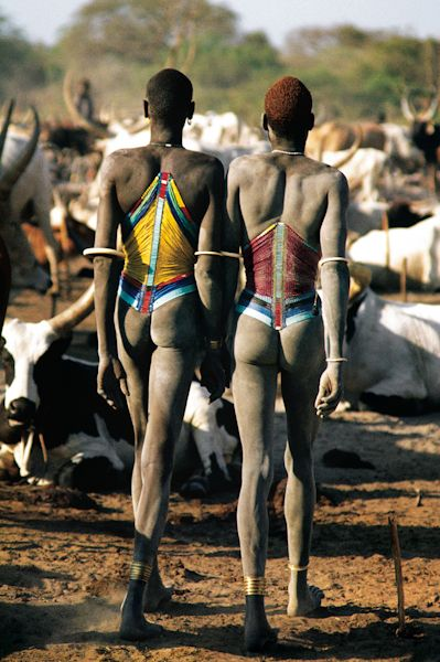 Dinka Men in Beaded Corsets, South Sudan - Dinka men from South Sudan often walk through the cattle camps hand in hand. This physical touching celebrates their close bonds as age-mates. Their traditional corsets are color coded to show their status in life: a red corset indicates a young man 15 to 25 years old, while a yellow one shows he is over 30 years old and ready for marriage. 1979