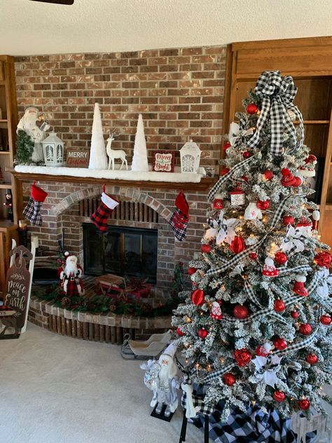 Frosted tree with ribbons of white and black plaid, red bulbs, ornaments of sweaters, hats, booties, mittens, and plaid poinsettia picks. Topped with a full white and black plaid bow with ribbons streaming down. #plaidchristmas #christmastreeideas #christmastrees