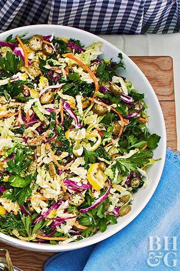 Classic cabbage coleslaw is a crowd favorite and this twist on the favorite is no exception. We've added new flavors like banana peppers, pickled okra, and fresh chives to this unique summer side dish. #memorialdayideas #memorialdayparty #sidedishideas #partysidedish #bhg