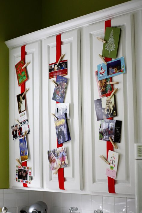 """Good idea for Christmas cards! Attach ribbon to kitchen cabinets. Use clothespins to hang cards. This is from the blog """"Greener Grass."""""""
