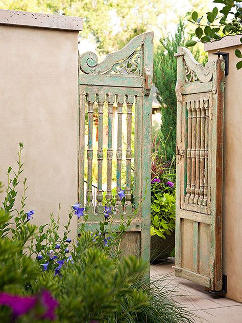 the turned wood spindles make a window in this garden gate. Seems very romantic/old-fashined and nicely set in the stucco wall.
