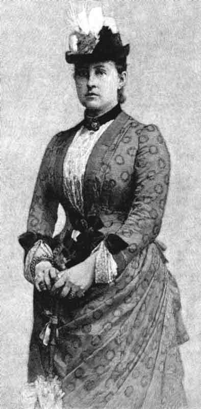 Queen Olga wears early 1890s style day dress with a jacket bodice over a chemisette with V-shaped cuffs. The bows along her waist suggest her dress has a V, not shallow V, waistline