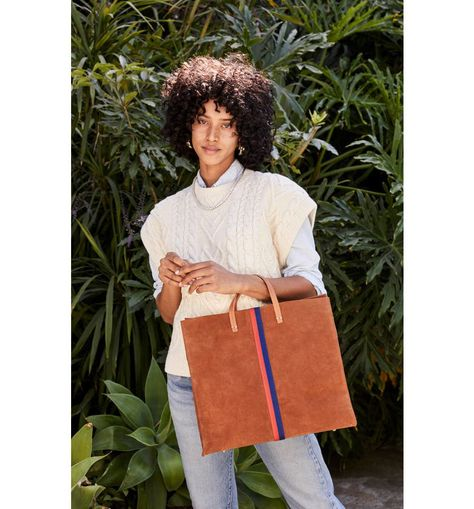 Vibrant stripes add a pop of modern style to this spacious and sophisticated suede tote.