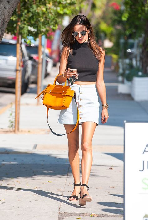 Judging by her latest street style ensemble, Alessandra Ambrosio is all in favor of the '90s fashion revival going on right now. The model (who just completed an amazing week of stylish looks) was spotted wearing two hot throwback trends while walking around Los Angeles: a light-wash, A-line jean miniskirt and a sleeveless turtleneck crop top.