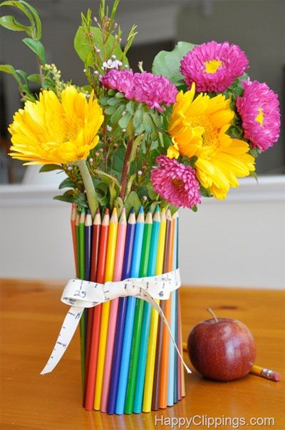 I first wrapped a few colored pencils around a (soup) can and secured with a rubber band. I then continued to insert more pencils all around the can. Note: You could probably use any container (such as a glass jar)  that can hold flowers as long as you can easily wrap a rubber band and pencils around it.
