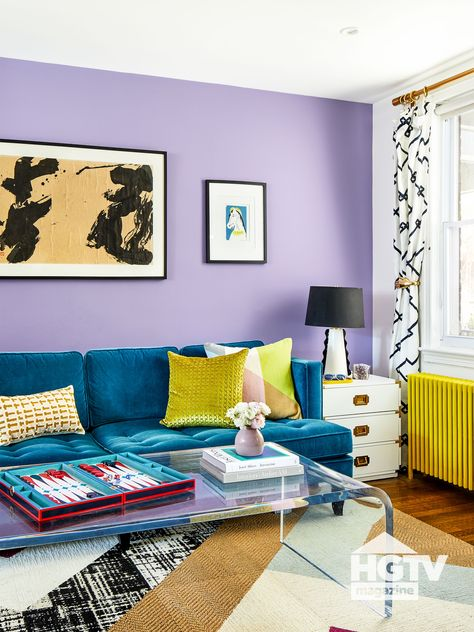 A blue velvet couch and yellow throw pillows pop against bright purple walls in this modern chic living room. See more on HGTV.com.