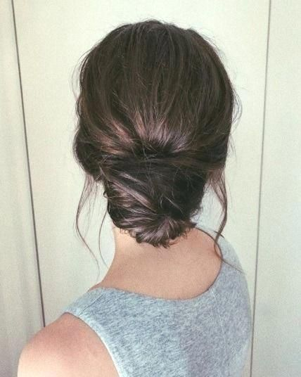 Back View Of A Brunette Woman Wearing A Grey Top With Her Hair In A Low Textured Messy Bun Hairupdos Back View O Hair Styles Long Hair Styles Bun Hairstyles