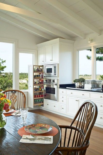 Bright beach house kitchen with many large windows to capture the view