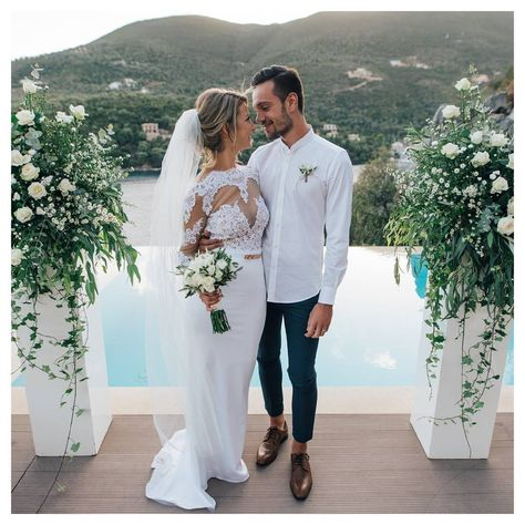 Classical ceremony columns with green and white flowers for villa wedding in Greece on a terrace overlooking the sea in Sivota Bay. By Lefkada Wedding Planner - Lefkas Weddings