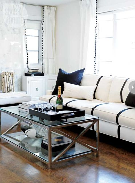 White and Black Living Room with white sofa with black trim (grosgrain ribbon + hot glue gun) and white drapes with black pompom trim - Erica Cook via Style and Home