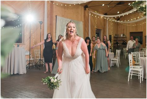 Bouquet toss in a barn during wedding reception | Sage Green and Gray Summer Wedding at Oak Hills | Jessie and Dallin Photography #utahwedding #utahweddings #utahweddingvenue #utahweddingvenues #utahweddingvendors #utahweddingphotography #utahbride #utahbrideandgroom #oakhills #mountainwedding #utahweddingphotographer #sagegreen #candidwedding #rockymountainwedding #weddingday