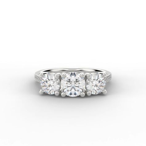 Three round brilliant cut diamonds, symbolizing a couples past, present and future, mounted into four claw settings with round diamond shoulders.  The centre diamond is 0.50 carat with each shoulder diamond being 0.25 carat.  This ring can be made with diamonds graduating in size or diamonds being of equal size (albeit prices will vary).