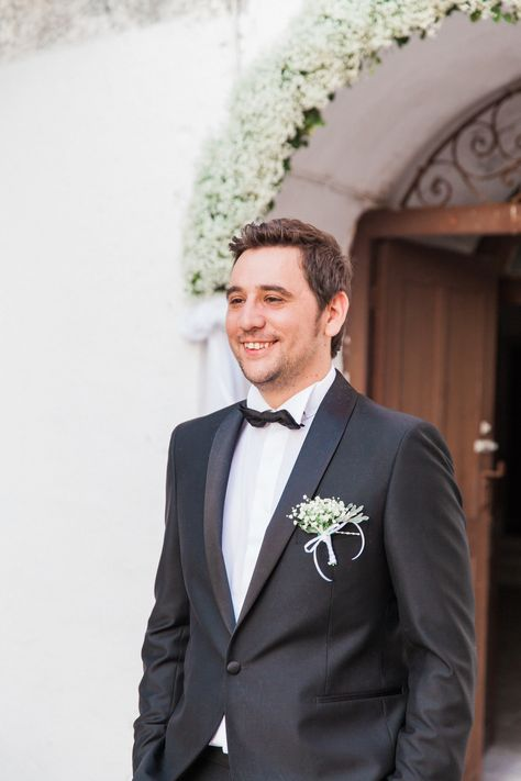 Grooms elegant look with a white gypsophila buttonhole and a black bowtie for his island wedding on Lefkada in Greece.