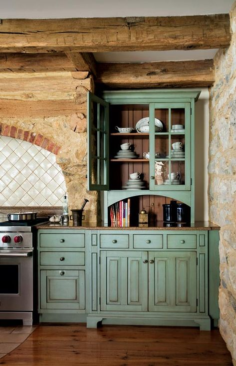 Primitive colonial kitchen cabinets--antiqued Sienna-green; cream-tile, raw wood.