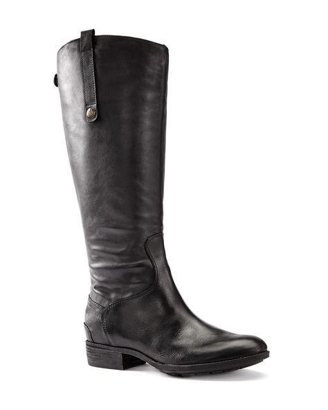 Cette botte haute en cuir tendance est essentielle pour l'automne et l'hiver ! Elle a un talon plat, une fermeture à glissière et des boutons-pressions. Elle s'agence à merveille à une jupe mi-longue ! Conçue pour un pied et un mollet larges.
