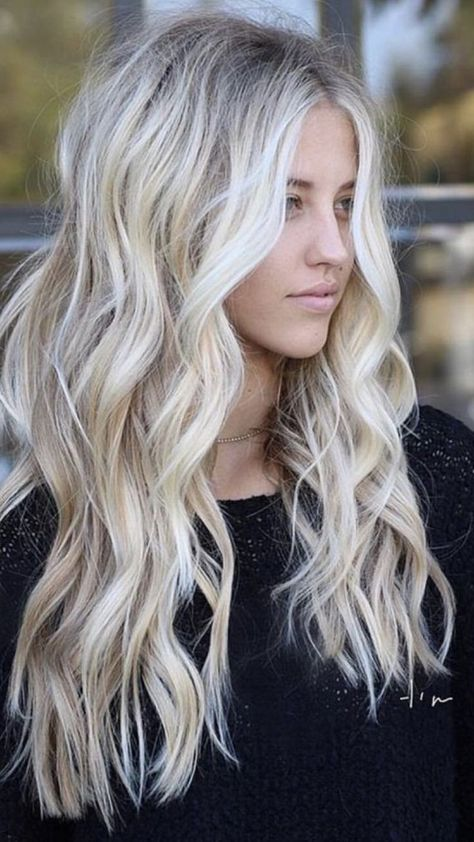 Long blonde hair with wand curl.