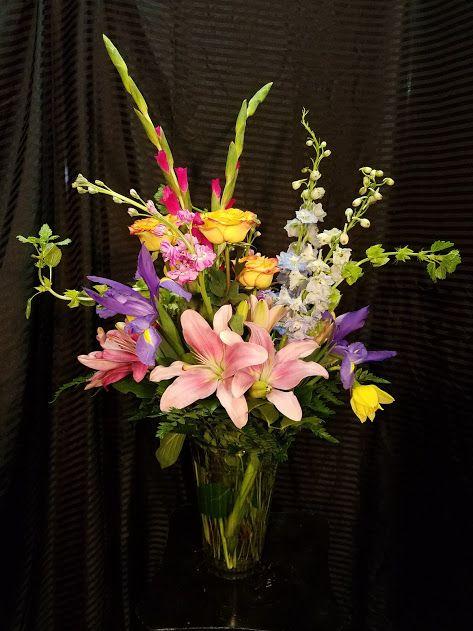 Big Spring Arrangement With Iris Bells Of Ireland Pink Gladiolus Blue Delphinium Purple Stock Yellow Rose Spring Arrangements Blue Delphinium Yellow Roses