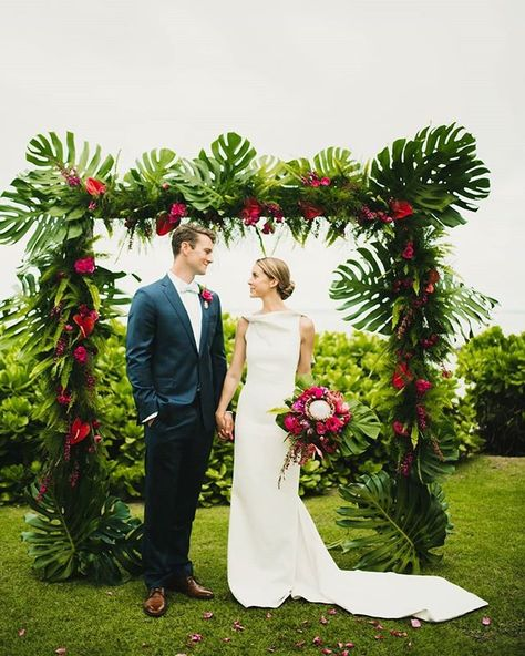We can't get enough of this stunningly tropical arch! Perfectly placed pops of bright fuchsia made this couple's special day unforgettable.  Moana Events  #monsteraleaf #weddingdecor #ceremonyarch #tropicalwedding #hawaiibride #destinationbride #destinati