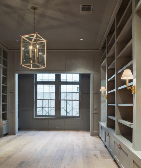warm gray office/study/library with brass fixtures and visual comfort sconces, light hardwood floors look raw and beautiful