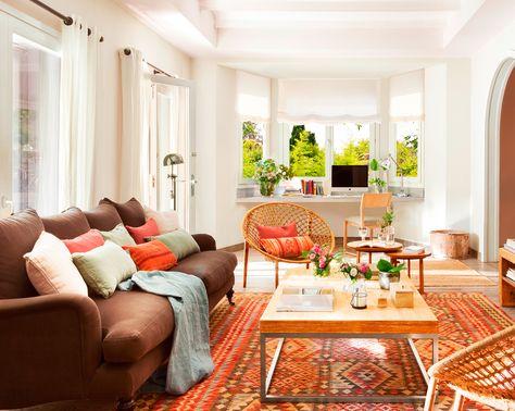 Salón con paredes y techo blanco, sofás, alfombra estampada y zona de trabajo bajo la ventana