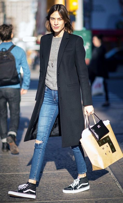 Alexa Chung wears a gray sweater, long black coat, skinny jeans, and high-top Vans sneakers