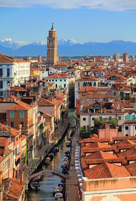 De Dorsoduro district in Venice with canal, traditional houses n small bridges. A campanile (with tilt) n de snowy mountains in de background. Venice, Veneto_ Italy
